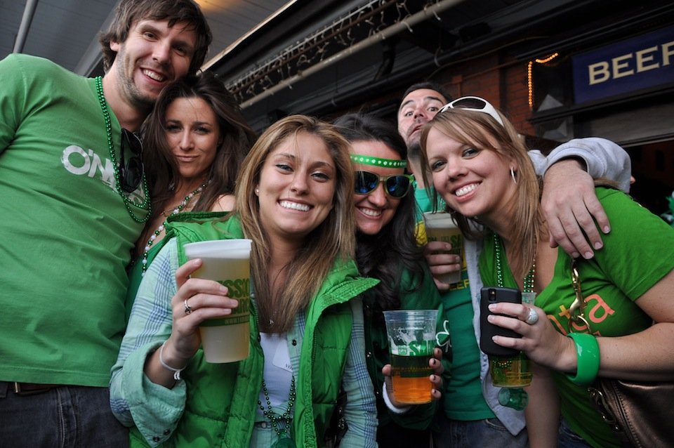 group of men and women wearing green and drinking beer